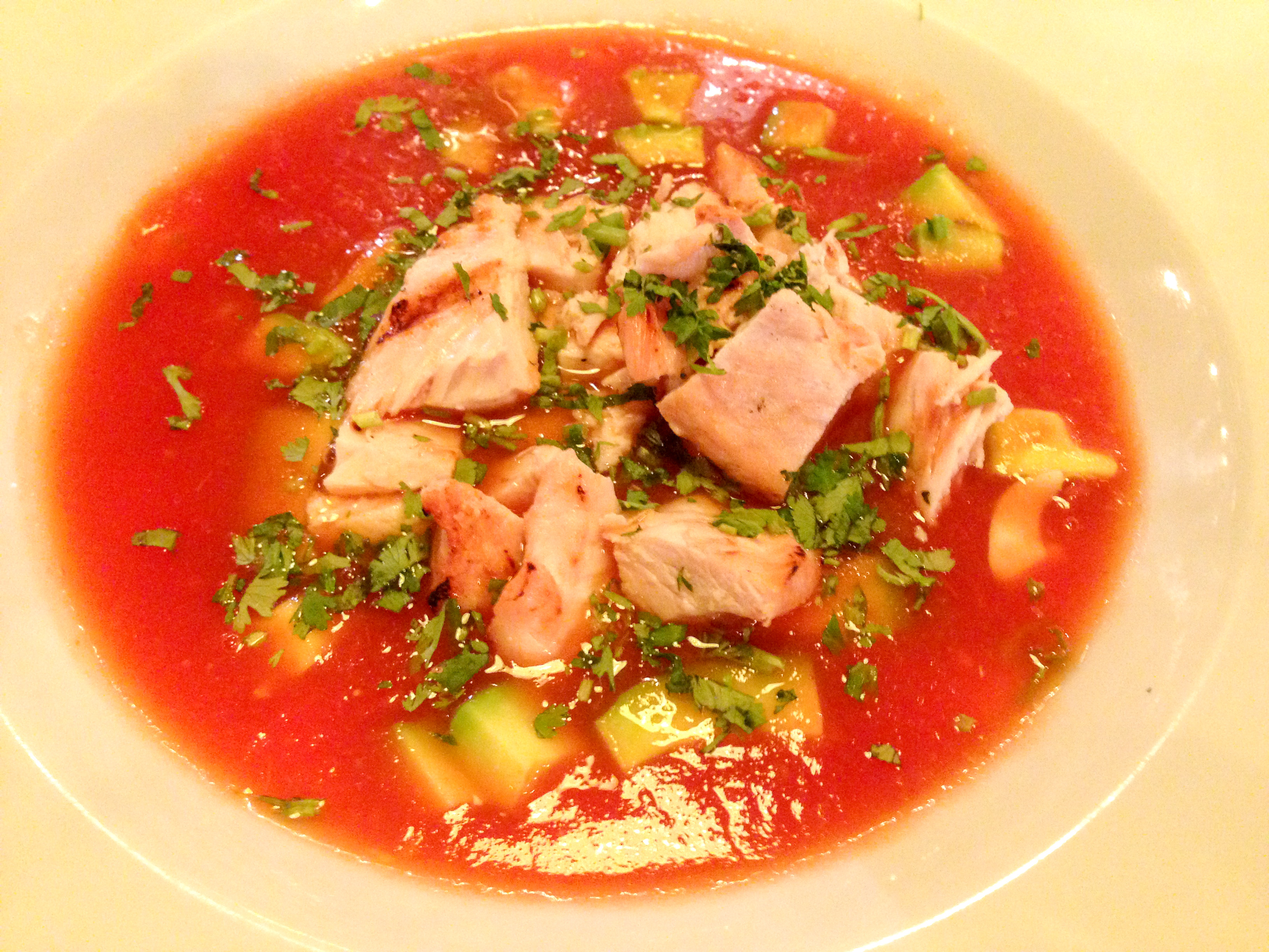Bowl of tomato soup with chicken and avocado